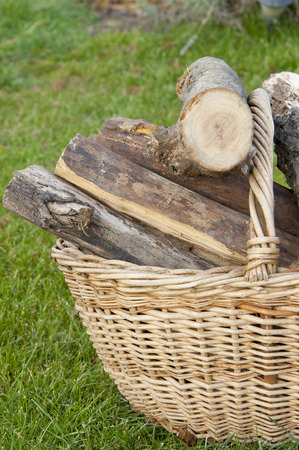 log basket: basket with chopped wood on the lawn Stock Photo