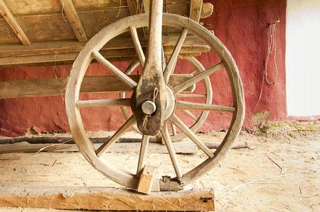 carreta madera: vieja rueda de carro de madera en un antiguo granero Foto de archivo