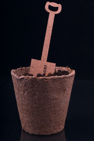 peat pot: peat pot with nutrient soil and decorative wooden shovel on a black background Stock Photo