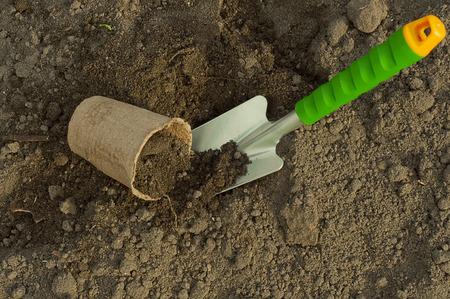 turba: pala verde y maceta de turba para las pl�ntulas en el suelo Foto de archivo