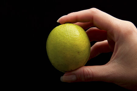 peppy: lemon in hand on a black background Stock Photo