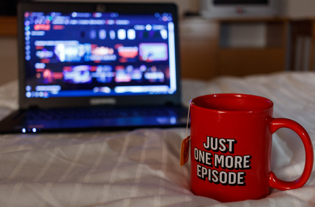 Watching series with a cup of tea. Inscription Just one more episode. Millennial concept Stockfoto