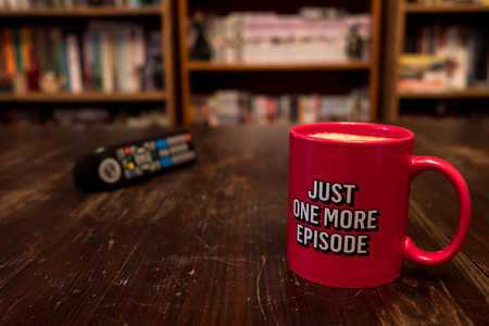 Red cup of coffee with inscription Just one more episode and tv remote controller Imagens
