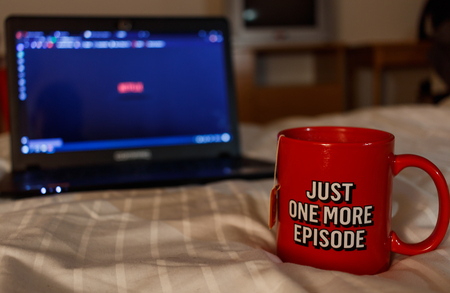 Watching series with a cup of tea. Inscription Just one more episode. Millennial concept Standard-Bild