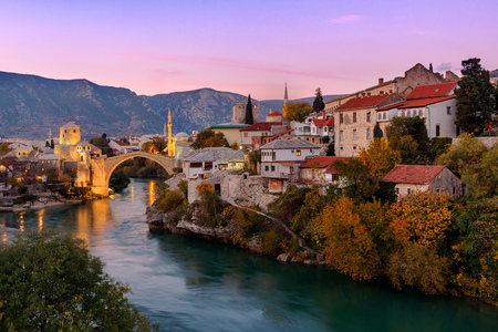 Skyline of Mostar with the Mostar Bridge, houses and minarets, at the sunset in Bosnia and Herzegovina.p