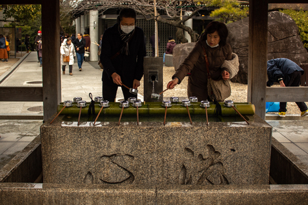 OSAKA, JAPAN - JAN 29, 2018: Japanese people doing Chozuya water purification rite in temple of Osaka Editorial