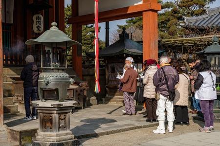 NARA, JAPAN - JAN 30, 2018: Japanese people praying on temple of Nara