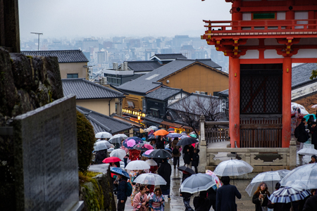 KYOTO, JAPAN - 10 FEB 2018: Aerial shot of people walking on a path at Kiyomizu Dera Temple wearing umbrellas