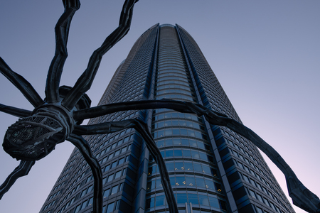 TOKYO, JAPAN - 15 FEB 2018: Maman big spider metal sculpture in Roppongi hills shot from below at sunset Editorial