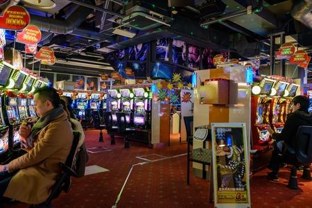 TOKYO, JAPAN - 16 FEB 2018: Japanese people playing in a Pachinko parlor of Shinjuku district