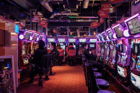 TOKYO, JAPAN - 16 FEB 2018: Japanese people playing in a Pachinko parlor of Shinjuku district at night