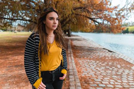 A young woman standing at autumnal park and looking at lake. Medium shot