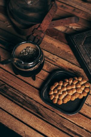 Argentine mate and cookies on wood. Style with vintage decoration of rusty metals and leather. Stok Fotoğraf