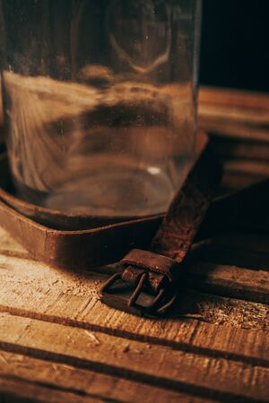 Vintage wooden stage, glass vase, rusty metals, old leather and rusty tools on a black background
