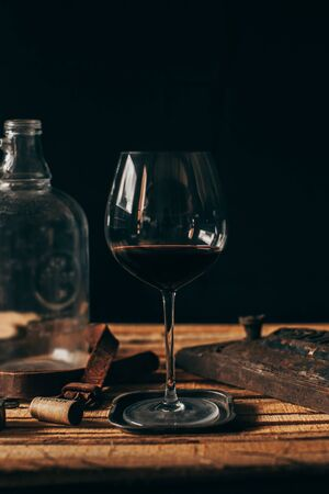 Wine glass on wood with black background. Style with vintage decoration of rusty metals and leather.
