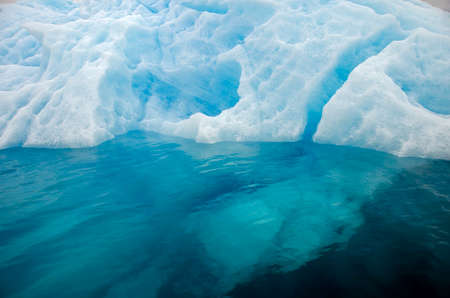 Detail of a bluish iceberg in clear water