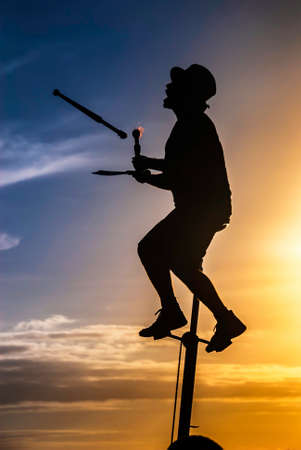 Silhouette of showman on a unicycle juggling with burning torches at sunset