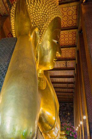 reclining: Reclining big Buddha gold statue in Wat Pho, Bangkok, Thailand