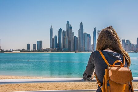 Young woman looking at the Dubai Marina from thebeach of Palm Jumeirah during a sunny day, Dubai, United Arab Emirates