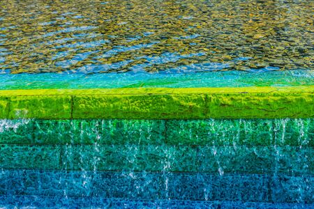 Bright fountain water on a green and blue wall with sun reflection background, Zabeel Park, Dubai, United Arab Emirates 스톡 콘텐츠