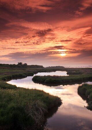 hengistbury: Sunset reflected in a river running through marshland on Hengistbury Head, near Christchurch, Dorset
