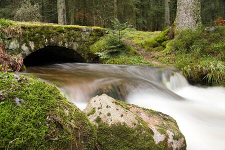 Waterfall with an old bridge, Vosges mountains in France photo