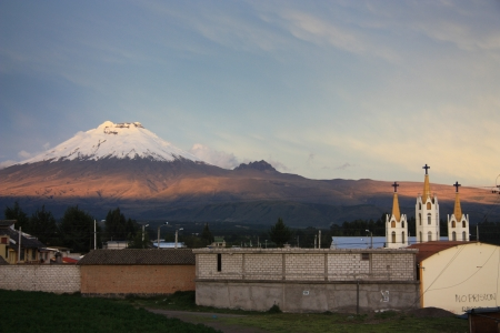Church with the Cotopaxi volcano at the background. Evening light. Ecuador. photo