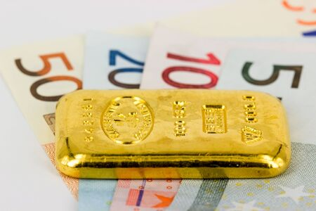 Gold bar standing on euro bank notes photo