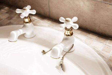 Close-up of white taps in the modern tiled bathroom. photo