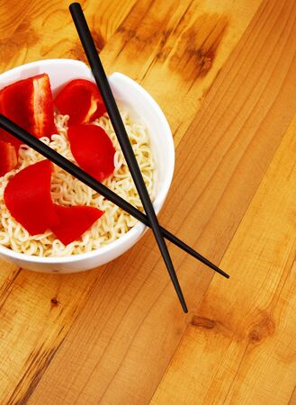 Chinece noodles with chop sticks in a bowl on wooden counter with some peppers in the noodles