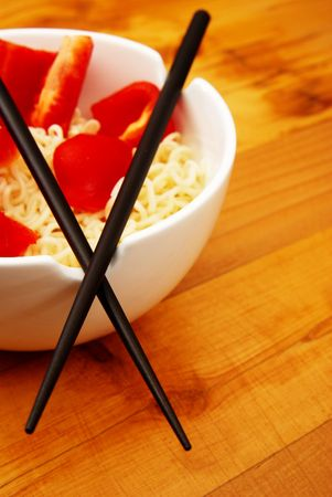 hashi: Chinese noodles with chop sticks in a bowl on wooden counter with some peppers in the noodles