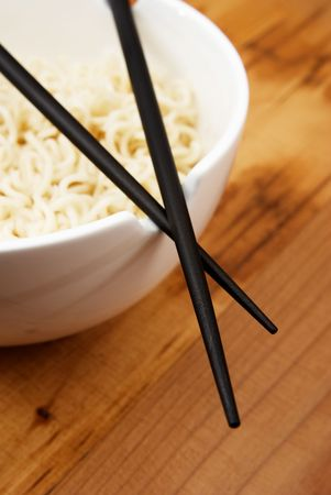 Chinese noodles with chop sticks in a bowl on wooden counter  Zdjęcie Seryjne