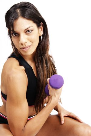 Beautiful brunette woman exercising with a purple dum bell photo
