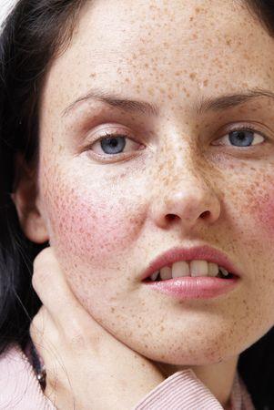 Portrait d'une belle femme brune avec les yeux bleu clair et taches de rousseur sur sa peau, portant veste d'hiver rose et foulard color?