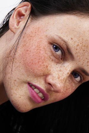 freckle: The face of a beautiful brunette woman with freckles on her skin, blue eyes and pink lips  Stock Photo