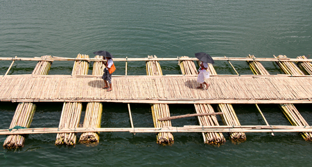 people walk on bamboo bridge across the river in Sangkhlaburi kanchanaburi Province Thailand photo