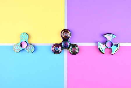hyperactivity: Group of hand fidget spinner toy on colorful and trendy background. Stress and anxiety relief.