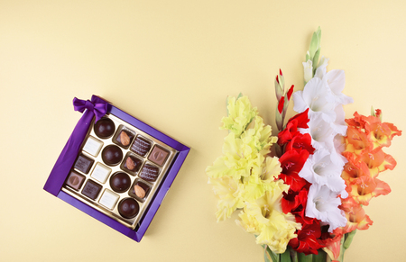 Beautiful gladiolus flowers on yellow background with delicious chocolate candies in gift box.