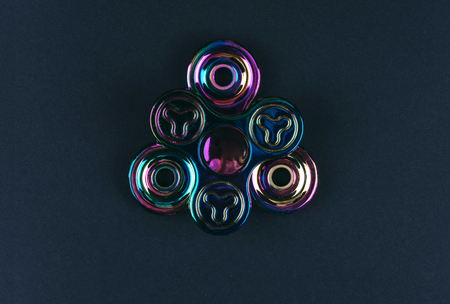 Group of hand fidget spinner toy on black background. Stress and anxiety relief.