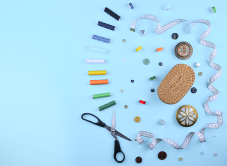 Background with stylish sewing tools and accessories on trendy blue background.