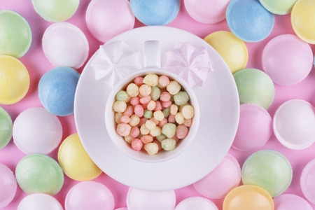 Small pastel color sweeties in a white cup on pink table. Stock Photo