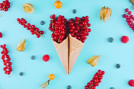 Berries in an ice cream cone on blue background. Flat lay style.