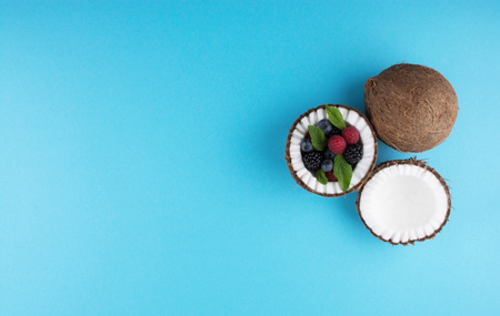 Fruits of coconuts on blue background with mix of berries. Colorful diet and healthy eating concept. Flat lay style. Stock Photo