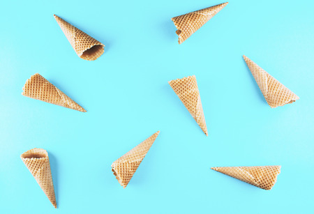 Empty ice cream cornet on blue background. Flat lay style. Stock Photo