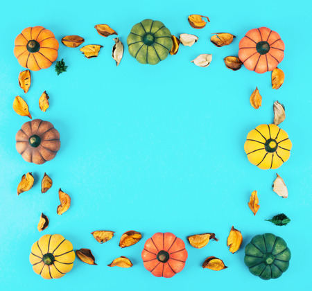 Decorative pumpkins on trendy blue background with fall leaves frame.