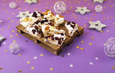 Traditional italian festive torrone or nougat with nuts on lilac background. Stock Photo