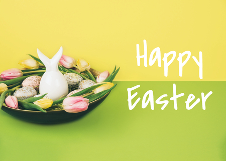 Creative easter composition with painted eggs and easter bunny on yellow and green background.