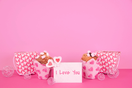 Tasty muffins in colorful paper baking cup with red hearts on pink background.