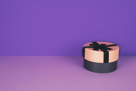 Pink gift box with ribbon on an ultraviolet background