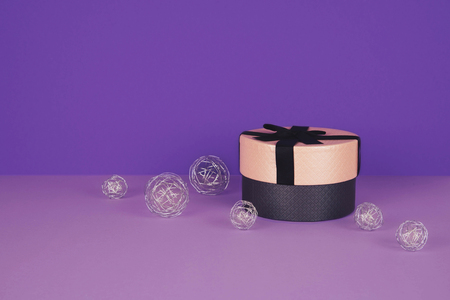 Pink gift box with ribbon on an ultraviolet background.